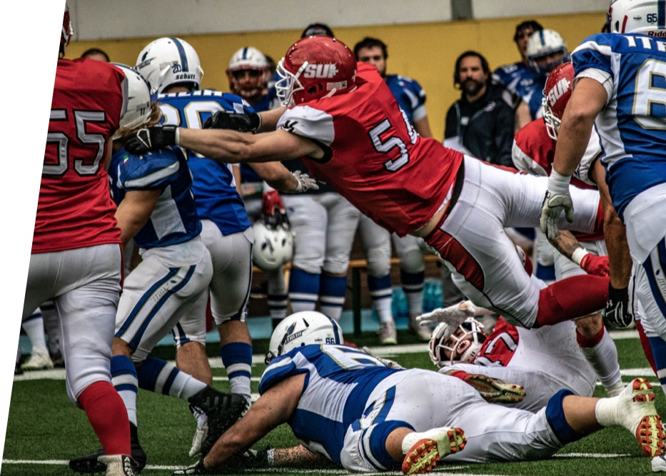 American Football player jumps over an opponent.