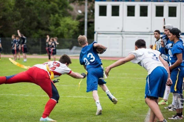 Flag football player is running, the defender trying to jump and catch the flag.