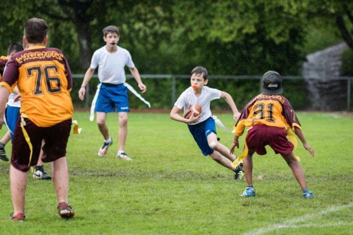 Children playing flag football. A boy runs with the ball fully concentrated.