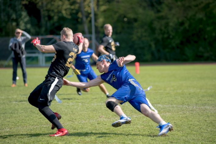 Two people playing flag football.